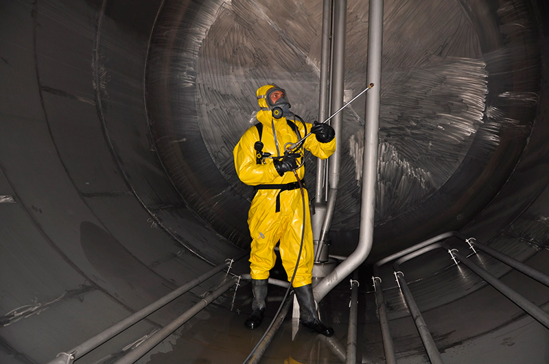 ladder safety - man in chemical suit inside  cargo tank on deck of chemical tanker for cleaning operation